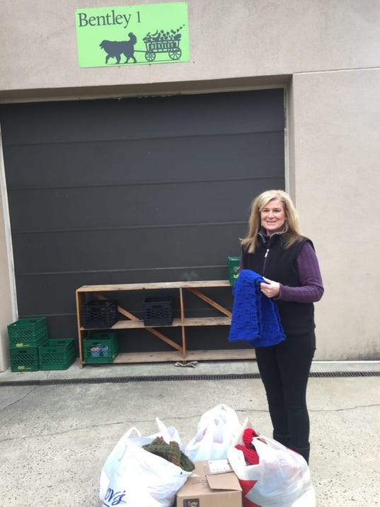 Here's Dorothy Stearns-Holmes, one of the founders of Bentley Community Services, holding a scarf and standing with the bags and boxes of hats I delivered to the Bentley warehouse on Wednesday.