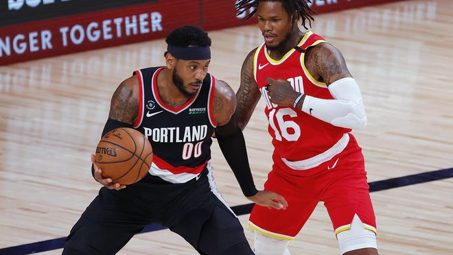 Portland's Carmelo Anthony (00) looks to drive on Houston's Ben McLemore during the first half of Tuesday's game in Lake Buena Vista, Fla.