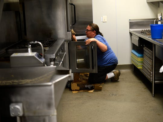 Resident Adam M. works on extra chores in the kitchen at the New Community Shelter in Green Bay on Wednesday.
