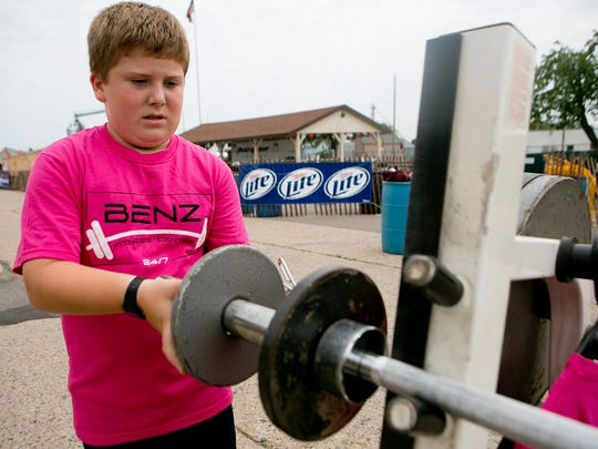 "Logan ""Chubs"" Stuttgen of Colby, 9, adds weight to the bar at the bench press competition Saturday during Colby Cheese Days."