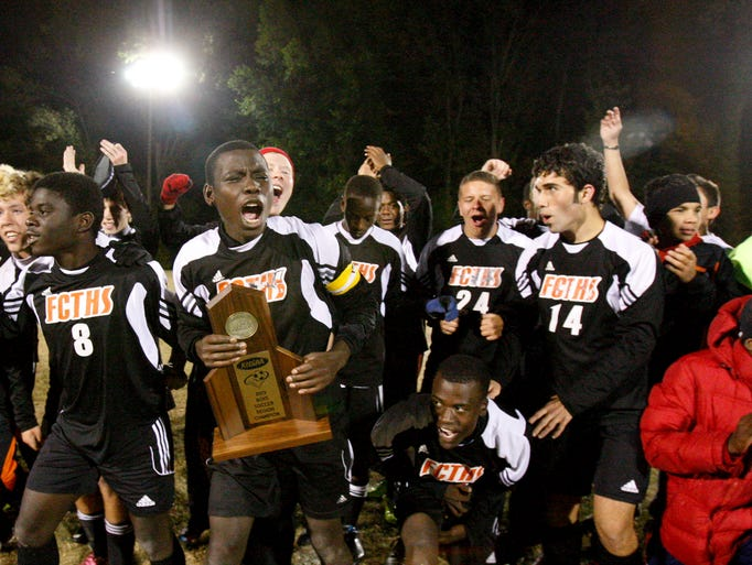 Fern Creek's Abdikidar Hussein, #4, hoists the 6th Region tropy after they defeated DeSales during their game at Male High School.     Oct. 24, 2013