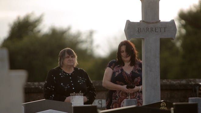 Emily Barrett (left) and Karen Barrett stand at the grave of Thomas Barrett, husband and father respectively, on Wednesday, July 2, 2014 in Cork, Ireland. In 1980 Private Thomas Barrett and other Irish soldiers were on a United Nations peacekeeping mission in southern Lebanon near the border with Israel when they were abducted by a Christian militia group. Other non-Irish personnel in the convoy were released, but the Irish soldiers were separated. Private John O'Mahony was shot, but managed to escape. Privates Derek Smallhorne and Thomas Barrett were tortured and killed. O'Mahony and a former Associated Press correspondent who was there that day identify one of their abductors as Mahmoud Bazzi, who later entered the U.S. illegally and has been living in Dearborn, Mich. Bazzi was arrested on Tuesday, July 15, 2014 and is being held on an immigration violation. Families of the slain Irish soldiers and others in Ireland are calling for Bazzi to be deported and tried for war crimes. Bazzi denies all involvement. Brian Kaufman/Detroit Free Press