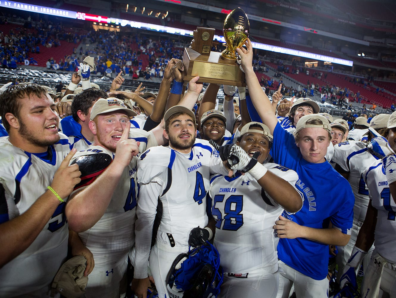 The Chandler high school football team celebrates at the University of Phoenix Stadium after their win over the Hamilton Huskies at the division 1 high school football state championships November 28, 2014 in Glendale.