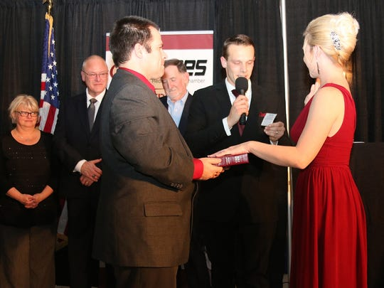 Redford Jaycees 2017 president Stephanie Johnson being sworn in by her husband Jay Johnson, assisted by brother Brandon Gilbert.