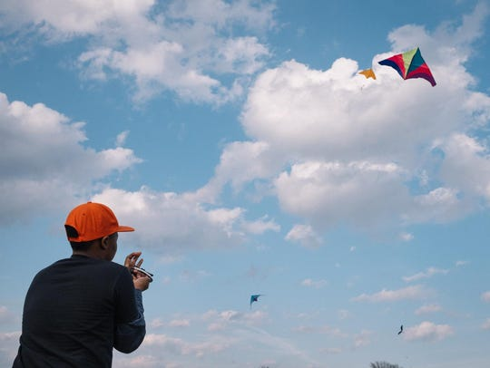 A boy flies a kite at a pop event put on by the Detroit