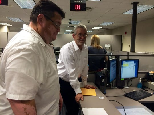 Rudy Armijo, left, and Don Pack request a certified copy of their marriage license minutes after tying the knot.