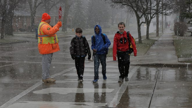 Oshkosh Crossing Guard Richard McDougal crosses students at the intersection of Bowen Street and Melvin, Wednesday, March 23, 2016.  The Oshkosh area may receive between 8 and 14 inches of snow.  A major snow storm coming from the west is dumping snow over the region.