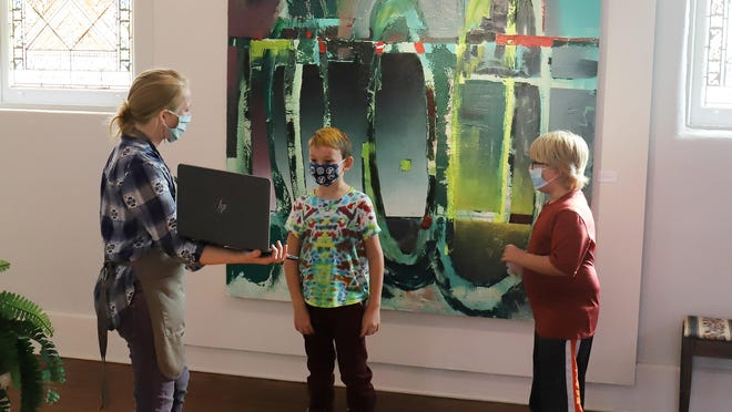 Center for Art and Education Curator and Educator, Amy Scoggins holds up a laptop for homeschool art students Jude Marshall and Noah Lohtinen, so they can talk with  Fayetteville artist Jody Travis Thompson via video conference, Monday, Nov 16, during the CAE's Homseschool and Afterschool Program held in front of Thompson' s painting on display in the CAE Main Gallery. The program includes studio work and exhibition tours. Jude is the 7-year-old son of Asherlee and Jeremy Marshall and Noah is the 8-year-old son of Maggie Lohtinen.