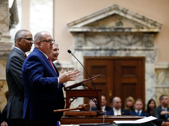 Maryland Gov. Larry Hogan addresses members of the state's House of Delegates in Annapolis on Jan. 1, 2018. Standing with Hogan are Maryland Lt. Gov. Boyd Rutherford, back left, and House Speaker Michael Busch, back right.