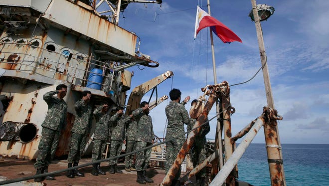 """Philippine marines deployed on the Philippine navy ship LT 57 Sierra Madre practice the """"relieving the watch"""" ceremony after the Philippine government vessel AM700 docked beside it off Second Thomas Shoal, locally known as Ayungin Shoal."""