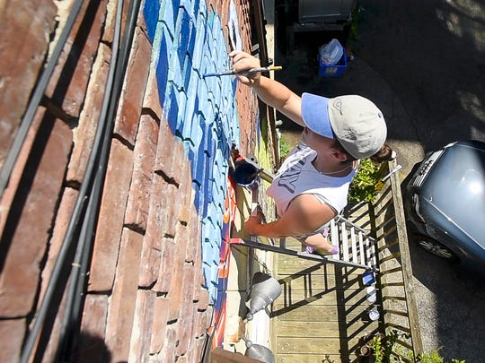Emily Herr paints a mural in the alley behind Battery Street Jeans in Burlington on Tuesday, August 1, 2017.  Herr has travelled to a number of cities painting murals that express positive images of women and girls.