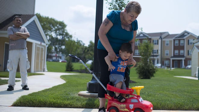 Resident Mercedes Collazo plays with her grandson Jaden Jimenes, 2, outside the Riverfront Village complex in Pennsauken Wednesday.