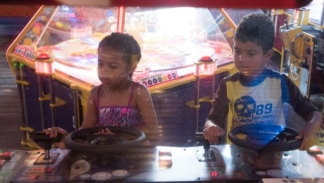 Naviah Burgee, 5, and her brother Paul, 6, of Westminster play an arcade game involving remote controlled cars at Marty's Playland on the Ocean City Boardwalk.
