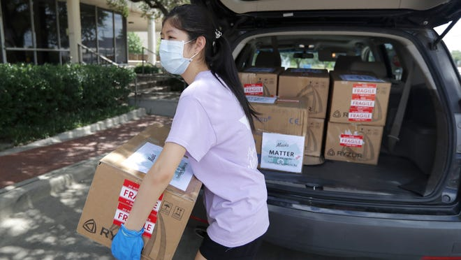 Valerie Xu, 15, delivers donated boxes of masks June 5  to UT Southwestern Medical Center in Dallas.