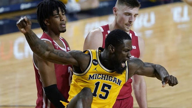 Michigan guard Chaundee Brown (15) reacts next to Wisconsin forwards Aleem Ford, left, and Micah Potter after a dunk during the second half of an NCAA college basketball game, Tuesday, Jan. 12, 2021, in Ann Arbor, Mich.