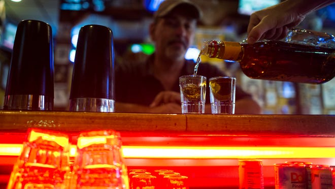 Bartender Robbie Gilroy pours shots of Fireball for a patron at Buxy's Salty Dog Saloon in Ocean City.