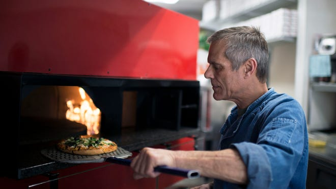Owner and pizza chef Ira Mensh removes a fresh pizza from his brick oven at Supremo Wednesday in Selbyville.