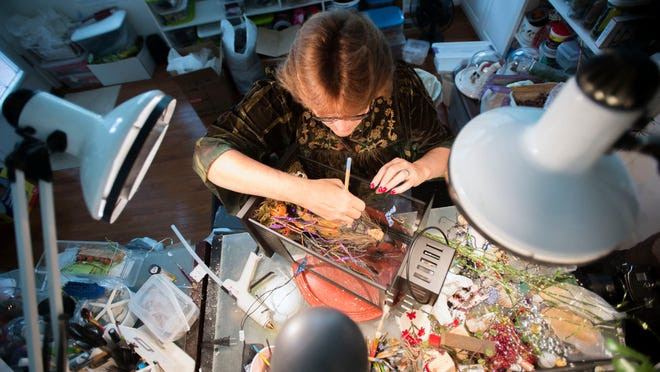 Dioramic artist Deborah A. Martucci places final touches on her Halloween-themed diorama in her Ocean View home studio.
