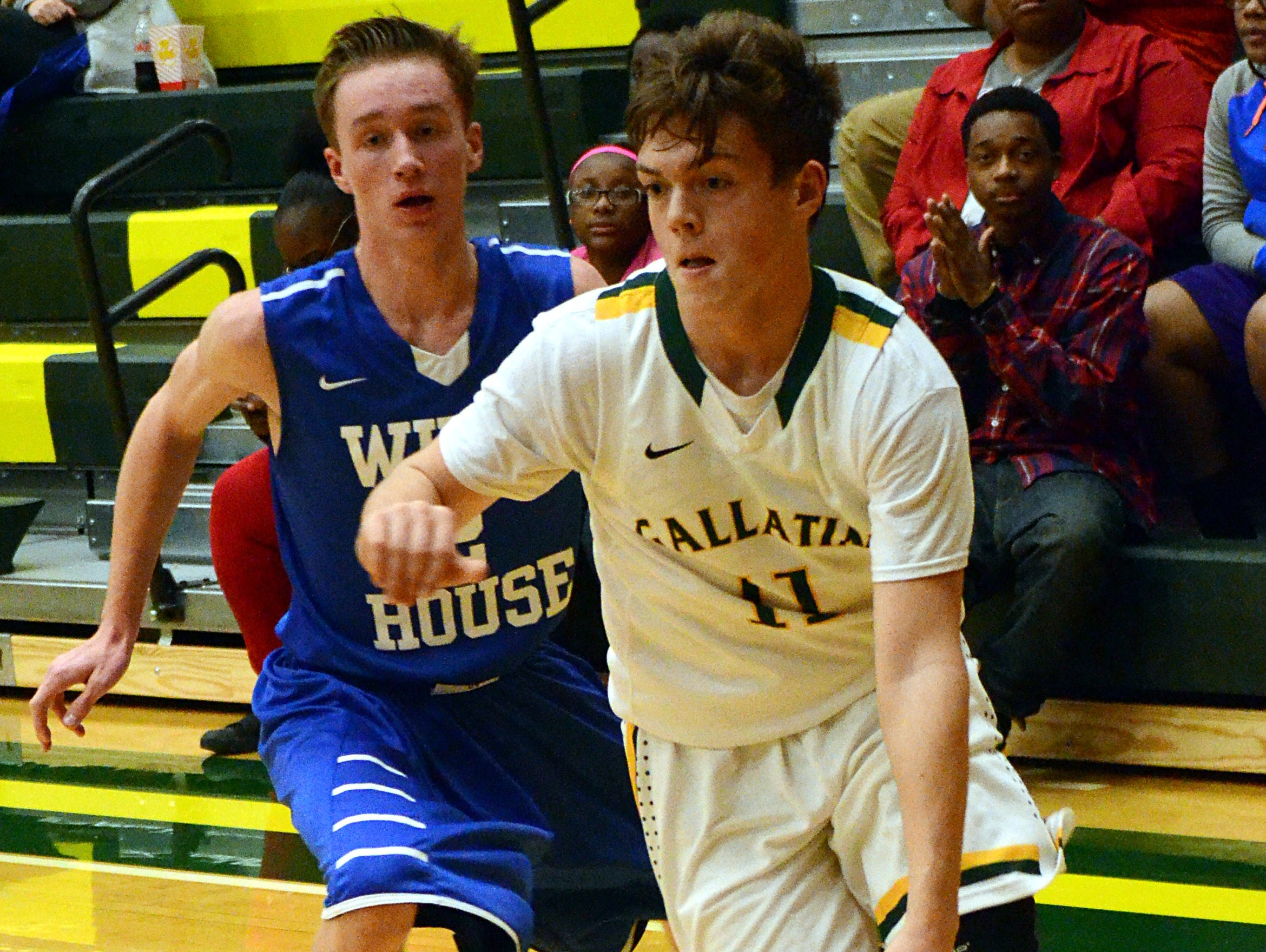Gallatin High sophomore guard Collin Minor dribbles to the basket during second-quarter action as White House freshman Jared Ward pursues. Minor scored 12 points in the Green Wave's 66-65 victory on Monday evening.