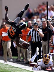Central Michigan defensive back Sean Bunting, right, watches as Oklahoma State running back Chris Carson gets airborn after jumping over him during an NCAA college football game in Stillwater, Okla., Saturday, Sept. 20, 2016.(AP Photo/Brody Schmidt)