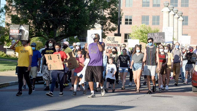 Sterling Brown leads about 100 protesters west on Walnut Street Thursday during the 11th night of protesting the death of George Floyd by a Minneapolis police officer.