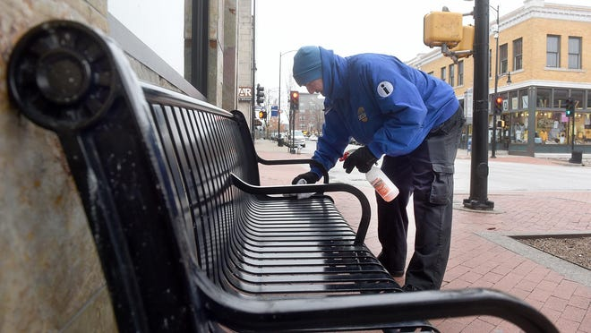 "Bill York, operations manager for the District Ambassadors Cleaning Program, cleans a bench on Ninth Street as part of the normal cleaning downtown and to guard against COVID-19. ""We make sure we get them extra good,"" York said of the public touch points of benches, cigarette recycling bins, trash cans and mailboxes."