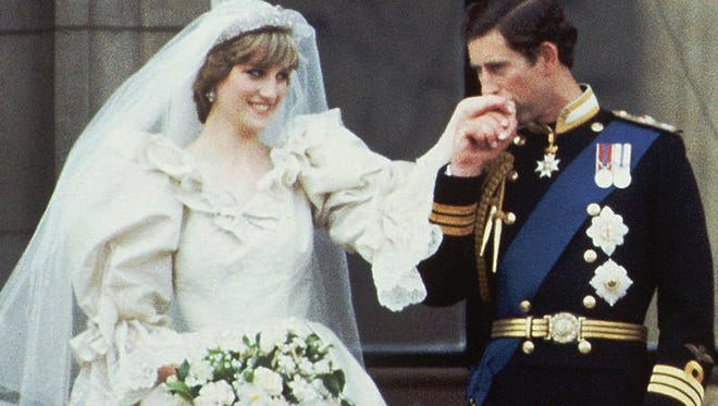 Britain's Prince Charles kisses the hand of his bride, the former Diana Spencer, on the balcony of Buckingham Palace in London after their wedding on July 29, 1981.
