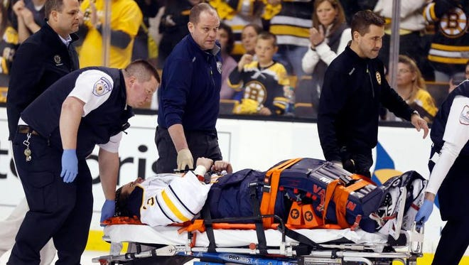 Sabres goalie Matt Hackett is wheeled off the ice after suffering an injury to his right leg in the third period at Boston.