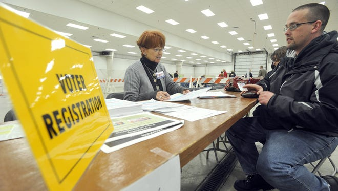 A poll worker helps a man register to vote in Fond du Lac in November 2012.