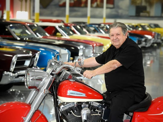 Willis Johnson stands among his classic car collection