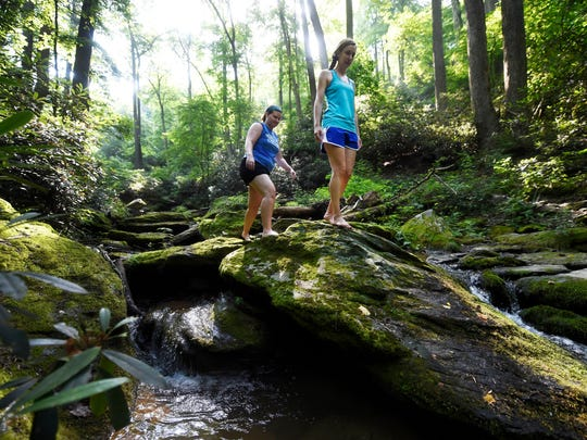 Sarah Wingard, left, and Brittany Spangler, both of Lancaster, explore the rocks and pooling water on the Kelly's Run Trail. The pair decided to explore the area after hearing about the trail from news reports of its reopening.