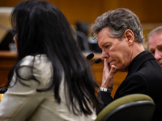 Randy Travis wipes his face as his wife Mary tells