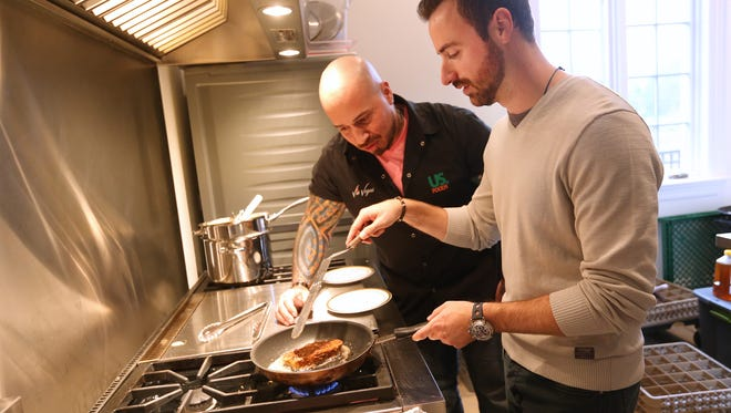 """IndyCar driver James Hinchcliffe and celebrity chef Vic """"Vegas"""" Moea make gingerbread French toast at the Rev tea"""