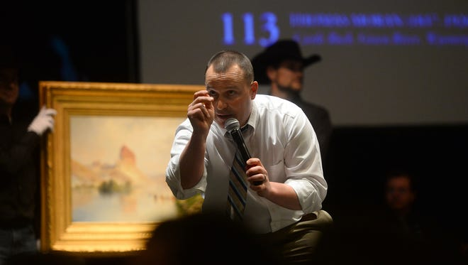 """Auctioneer Troy Black takes bids on the Thomas Moran painting """"Castle Rock, Green River, Wyoming"""" during The Russell live auction on Saturday night in the Civic Center."""