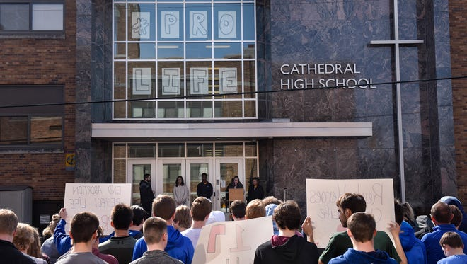 Students gather near the entrance to Cathedral High School Wednesday, April 11, during a pro-life walkout at the school in St. Cloud.