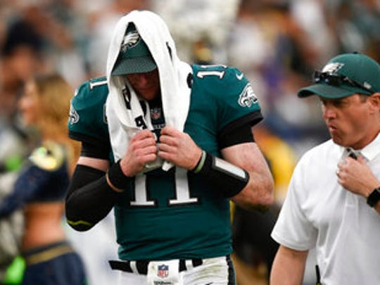 Eagles quarterback Carson Wentz leaves the field in the third quarter Sunday after suffering a knee injury.