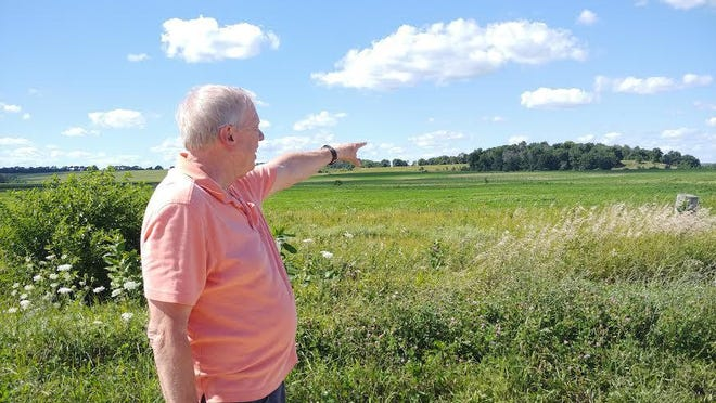 Durand resident Dennis Johnson stands on Wheeler Road Monday and points to the 5-acre site where one of two area hog farms may be built.