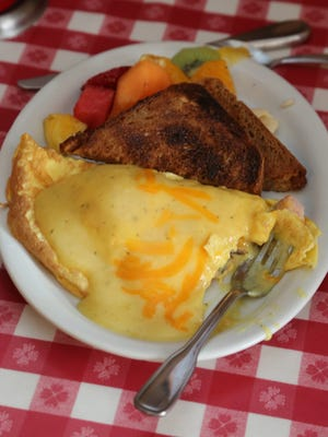 A diner has already taken a bite of her Benedict Omelette (a ham, mushroom and cheese omlette with Hollandaise sauce) at The Kitchen Table in Marshfield.