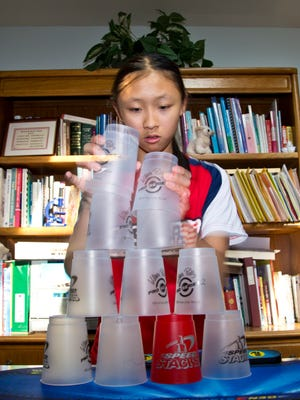 West Lafayette Junior High School student Christina Shi demonstrates the cup stacking abilities Wednesday that earned her national and world awards at her home in West Lafayette.