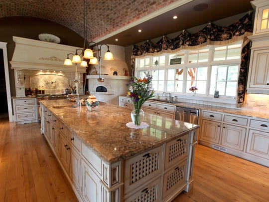 This spacious kitchen features a tiled barrel roll ceiling is over the island. There's a large, round pizza oven and the cabinets are carved cherry or antique-glazed white.