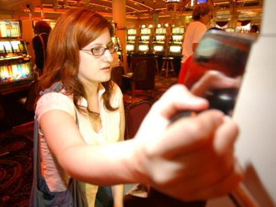 Amy Witherby pulls the handle for a slot machine while