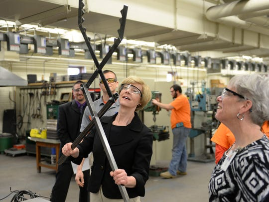 Sen. Tammy Baldwin looks at a prototype log grabbing tool as she talks about manufacturing technology during a tour of the Bay Link Manufacturing lab at West High School.