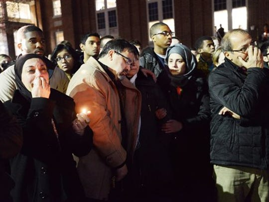 People attend a vigil for victims of a shooting at