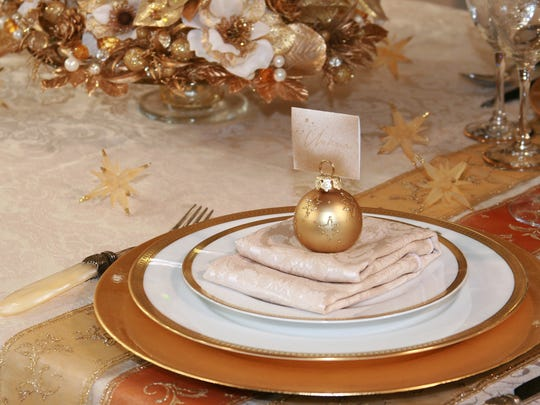 A gold-themed holiday table setting with a gilded floral centerpiece and glassware.