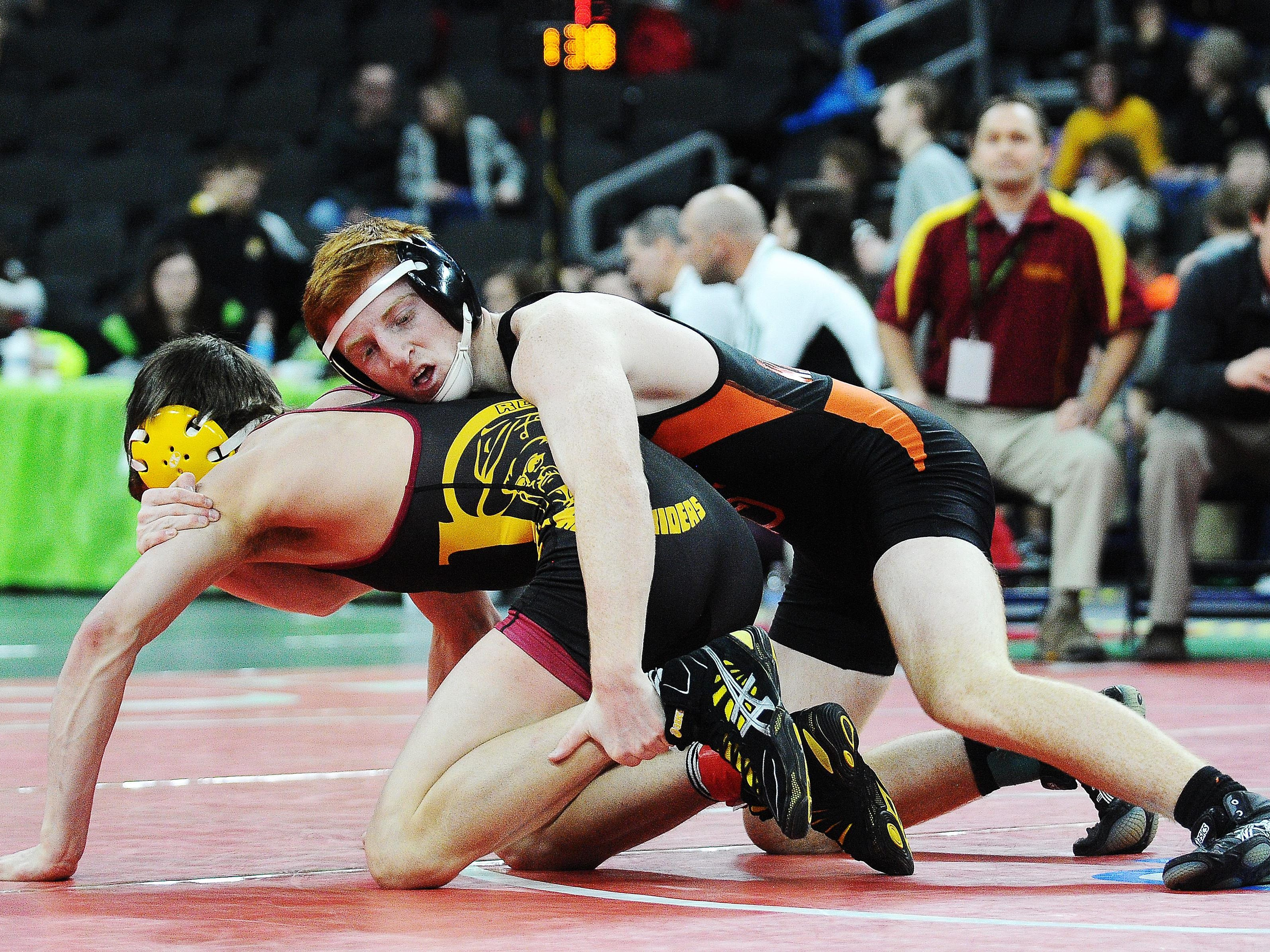 """Washington's Hunter O'Connor, top, wrestles Roosevelt's Carter Lohr during a 132-pound weight class match during the SDHSAA South Dakota State Class """"A"""" Wrestling Tournament on Friday, Feb. 27, 2015, at the Denny Sanford Premier Center in Sioux Falls, S.D."""
