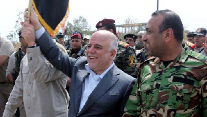 Prime Minister Haider al-Abadi, center, walks with