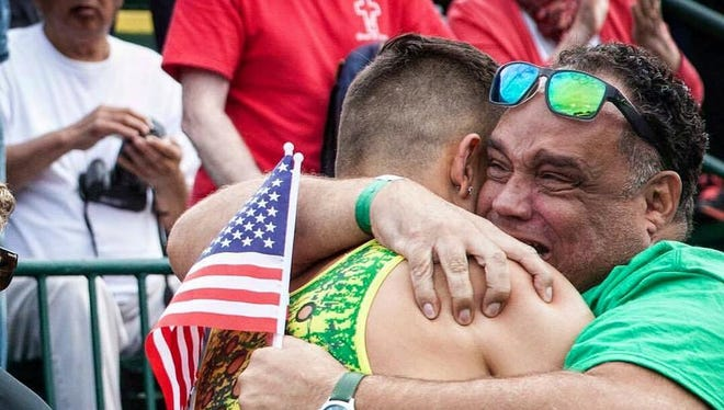 Brophy Prep grad Devon Allen embraces his father, Louis, after winning the 110-meter hurdles to advance to the Rio Olympics.