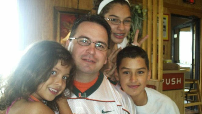 In a picture taken a few months before his death in 2007, Jose Bianchi, 42, is surrounded by his children (from left), Madison, 6, Mariah, 13, and Joey, 12.