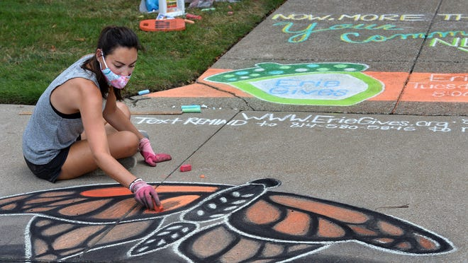 Helen Tullio completes a chalk mural Aug. 3 on the sidewalk in front of the Erie Community Foundation, 459 W. Sixth St. The mural was meant to draw attention to the 10th annual Erie Gives fundraising drive for nonprofits in the Erie region, which will be held Tuesday.