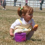 A youngster looks for Easter eggs during a 2012 event. Local Easter egg hunts take place Sunday.